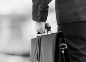 Kommerzieller Geschäftsmann mit einer Aktentasche, der einen Verkauf abschließen will