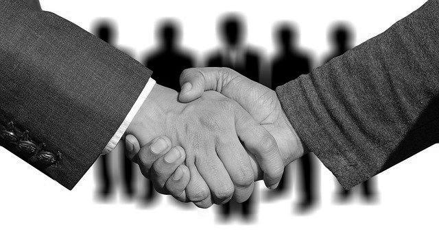Zwei Aktionäre in Anzügen schütteln sich die Hände, um einen Pakt zu unterzeichnen