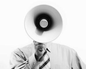 homme d'affaire tenant et communiquant dans un mégaphone