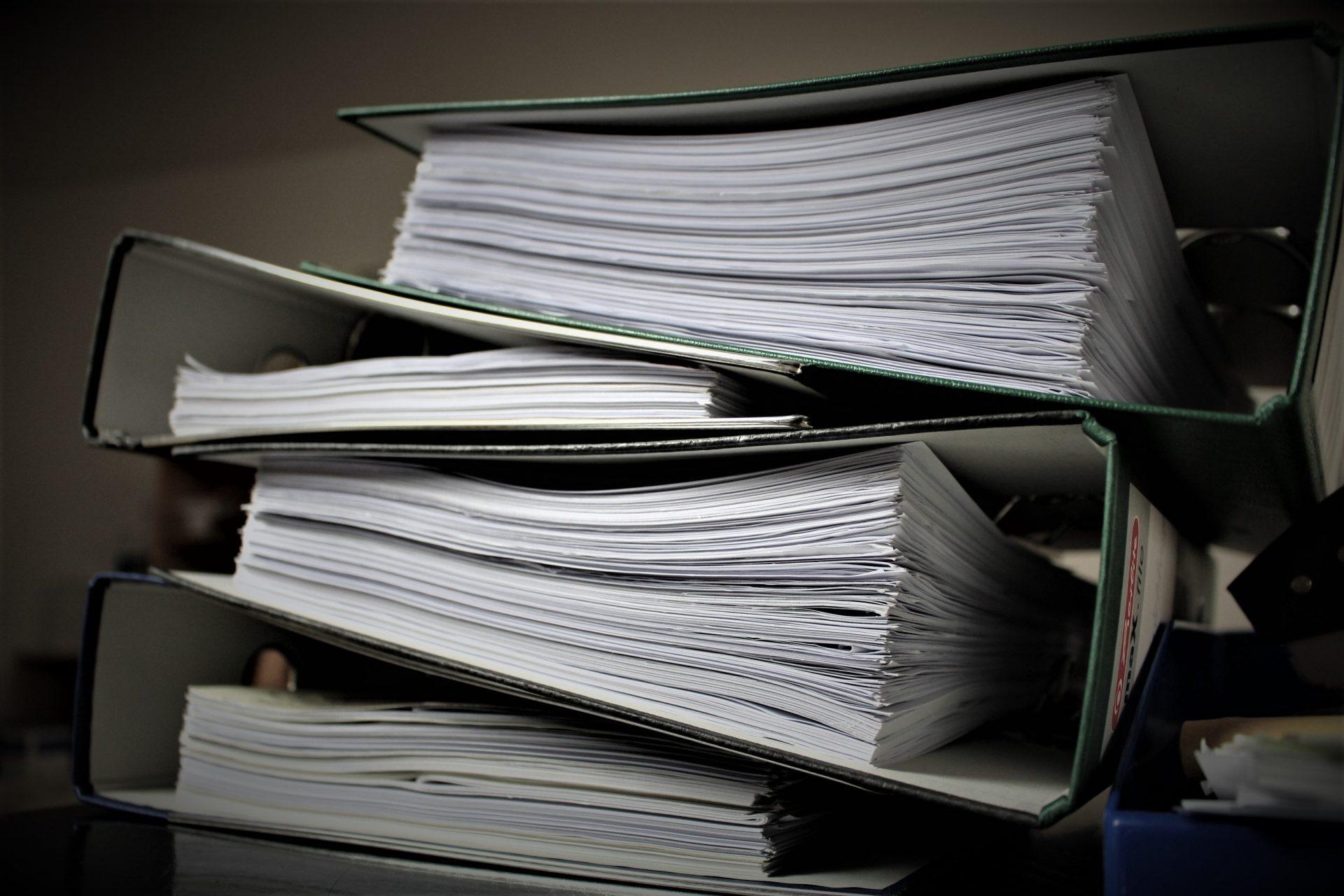 pile de gros classeurs avec des papiers administratifs