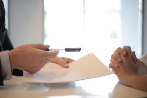 individu tendant une feuille et un stylo pour qu'un autre homme signe un contrat