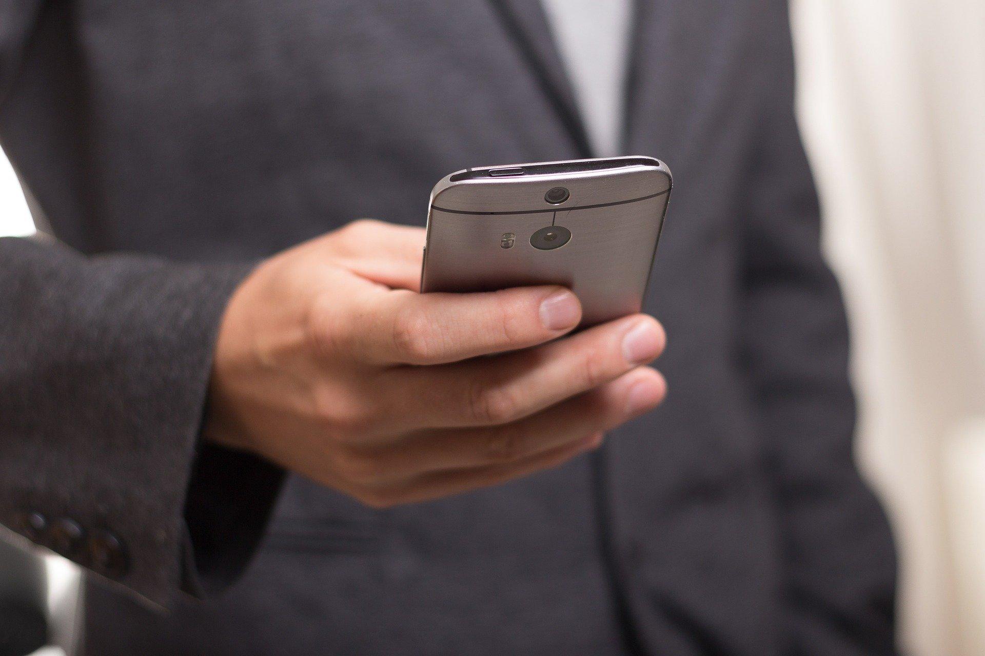 un businessman en costume consultant son téléphone portable
