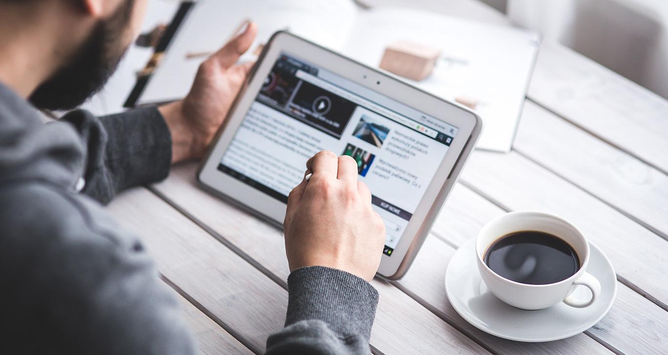 un homme regardant les actualités sur sa tablette