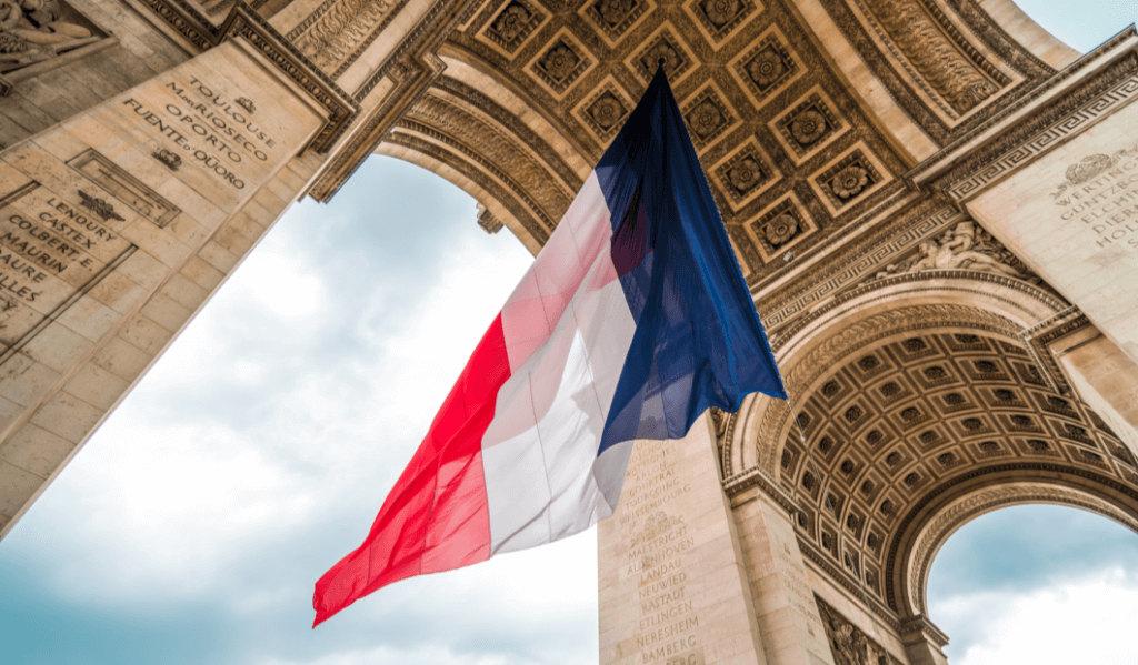 drapeau français au vent en dessus de l'arc de triomphe à Paris