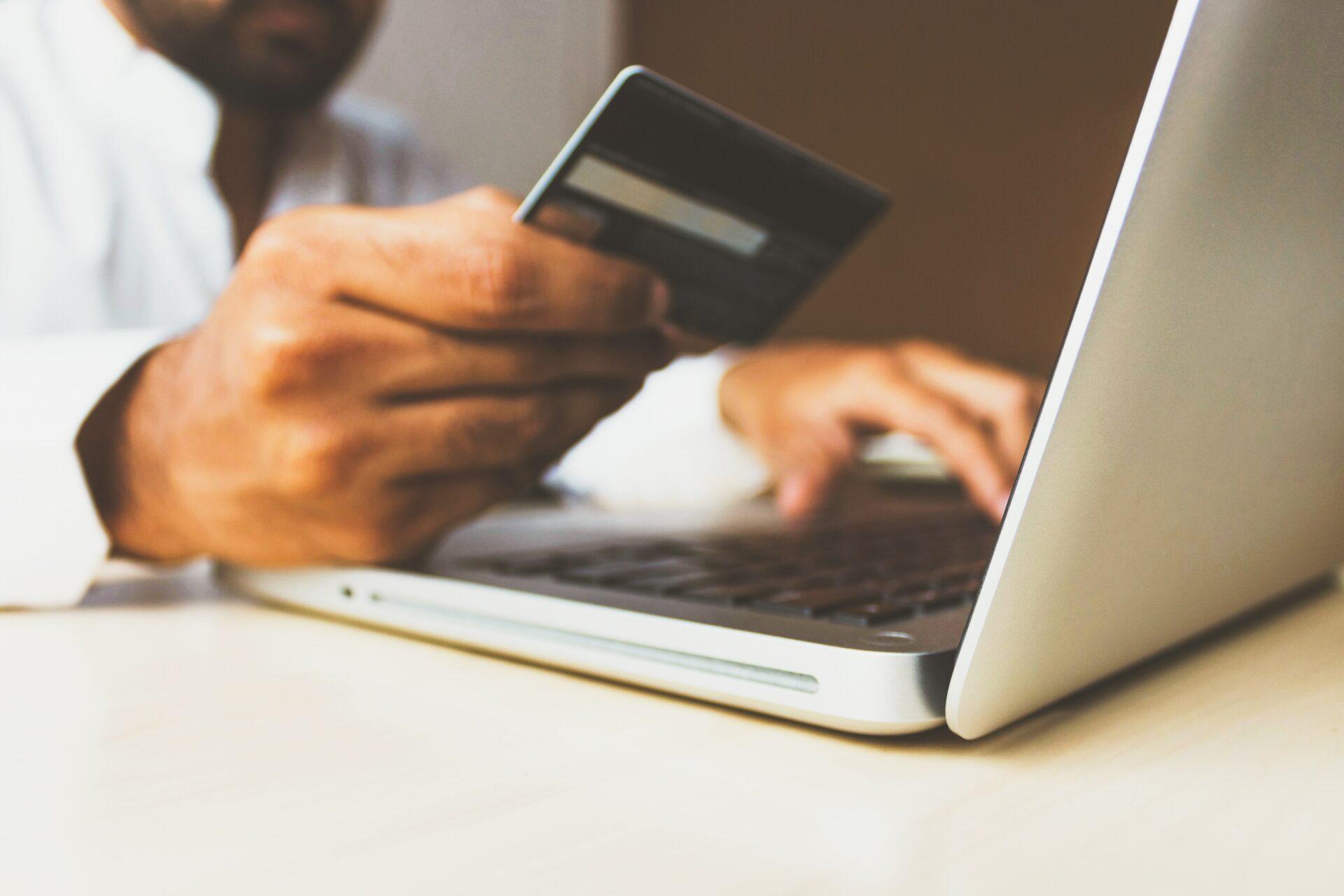 homme achetant en ligne grâce à sa carte de crédit depuis un ordinateur