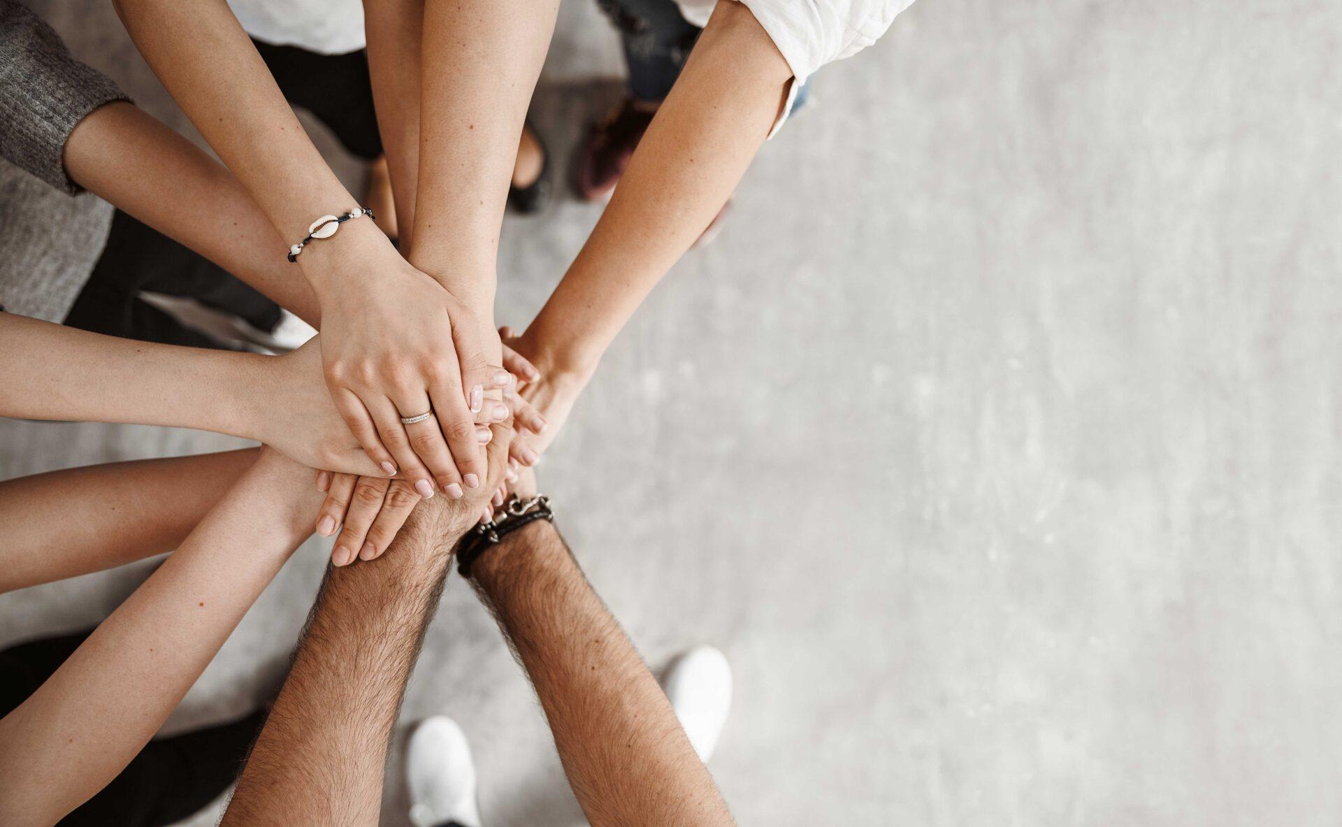 groupe de personnes en position de cris d'équipe avec les mains au centre