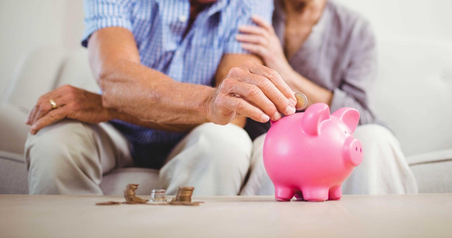 Secteur de la senior economy allemand seniors mettant une pièce de monnaie dans une tirelire