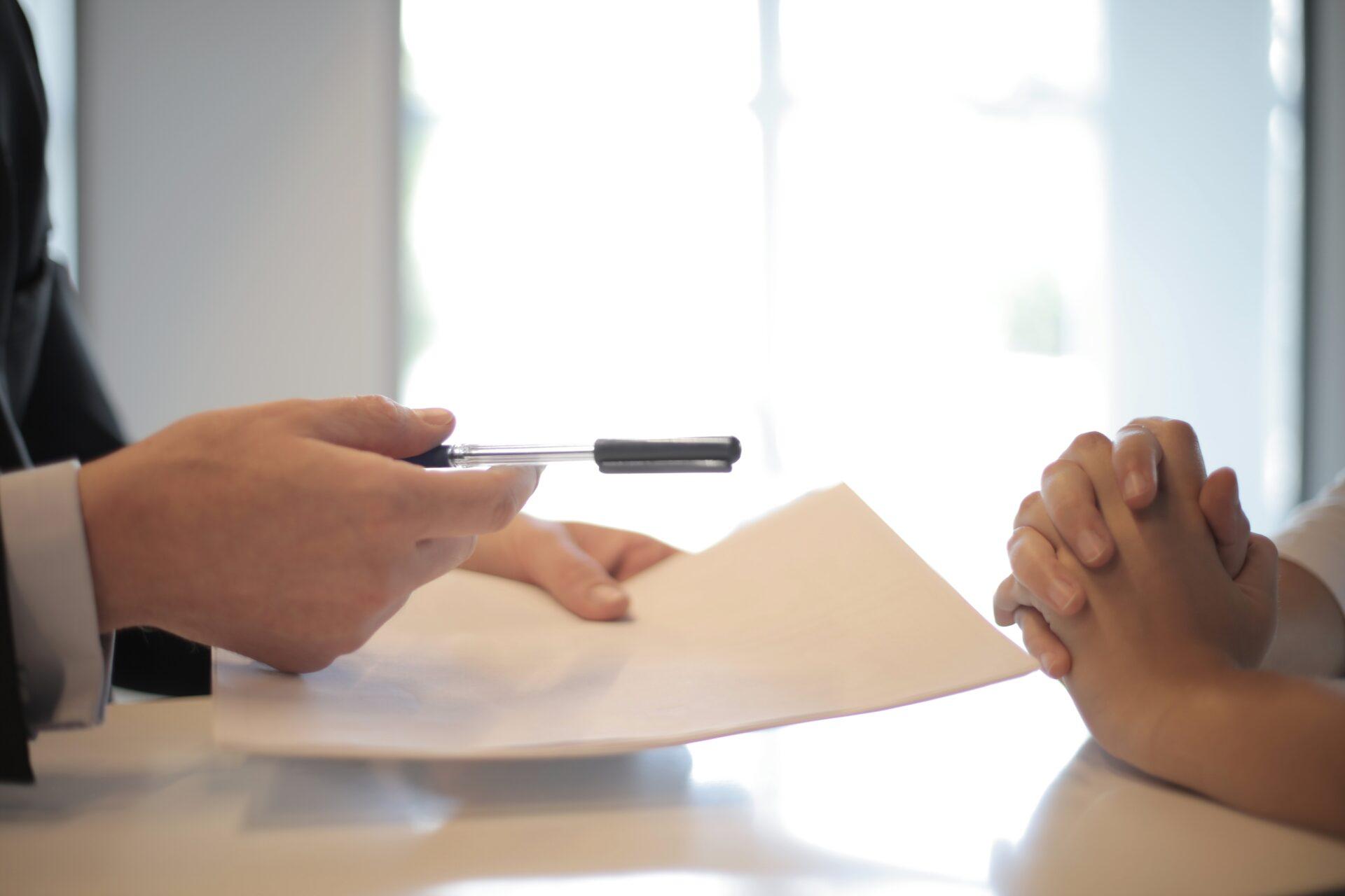 individu tendant une feuille et un stylo pour qu'un autre homme signe